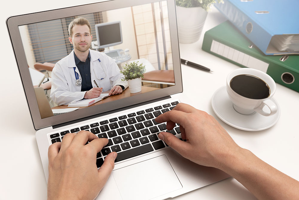 person on telehealth visit with doctor using a laptop
